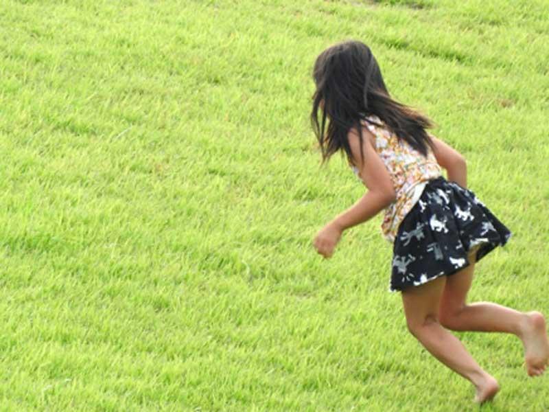芝の上で走っている子供のイラスト