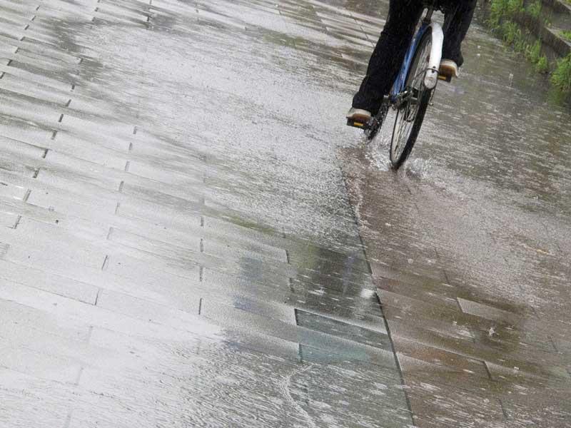 雨の中で自転車を乗っているお母さん