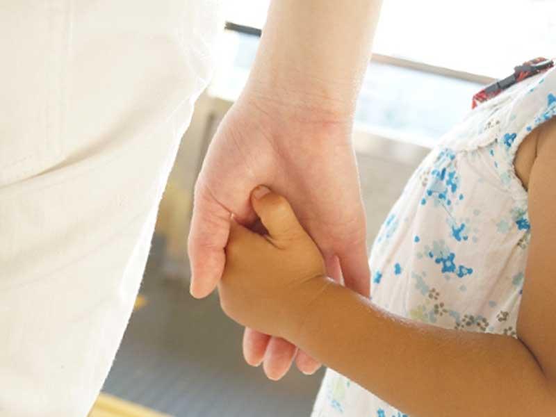 子どもの手を繋ぐお母さん