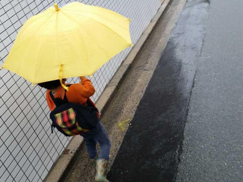 雨の中長靴を履いて歩いている子供