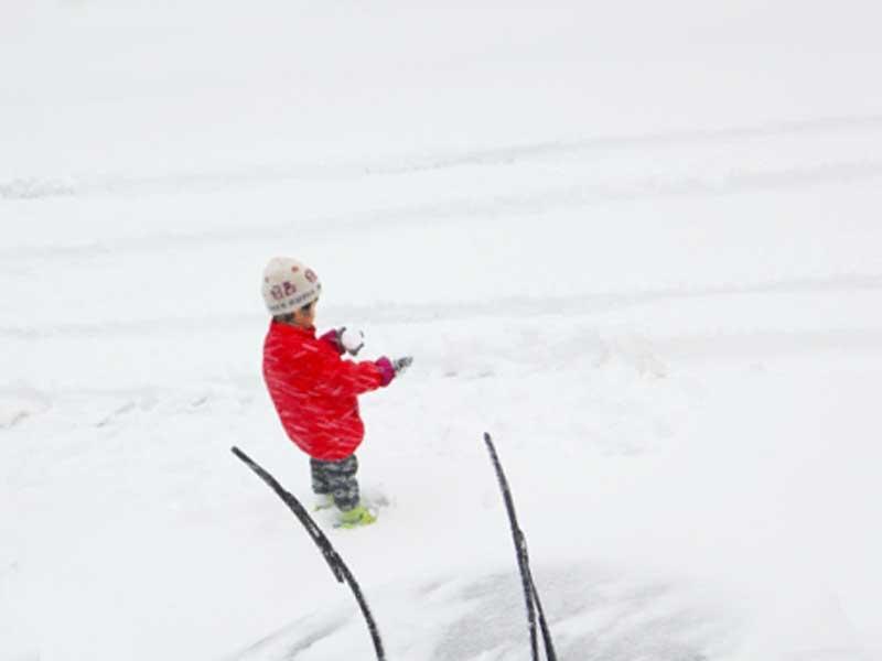 長靴を履いて雪の中で遊んでいる子供