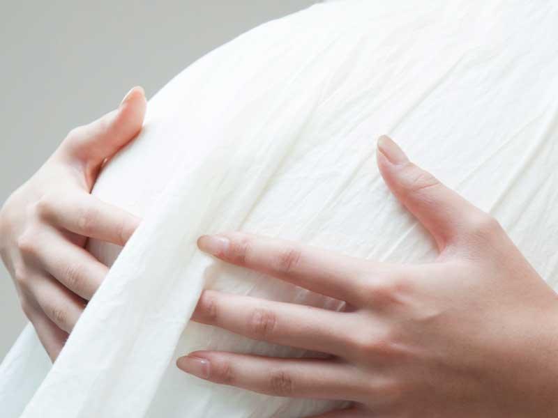 手でお腹を押さえる妊婦さん