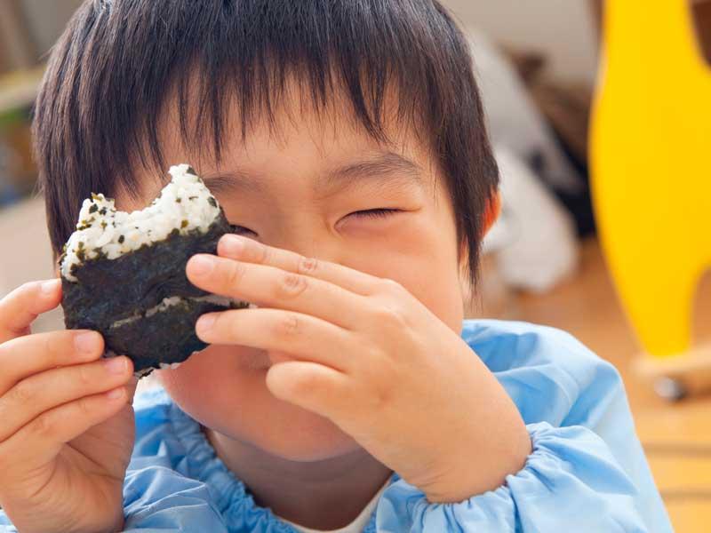 給食を食べている幼稚園生