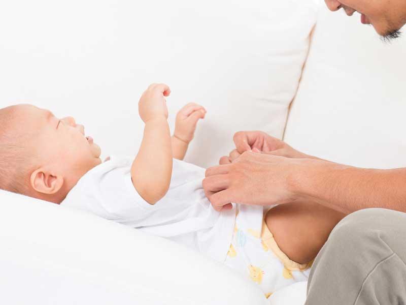 赤ちゃんのおむつ交換をしているお父さん