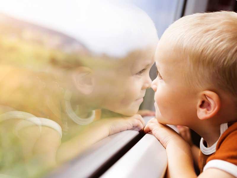 新幹線の窓から景色を眺める子供