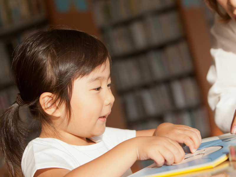 図書館で絵本を読んでいる子供