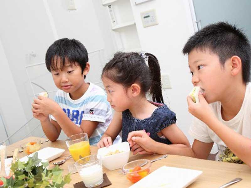 朝食でサンドイッチを食べる子供達