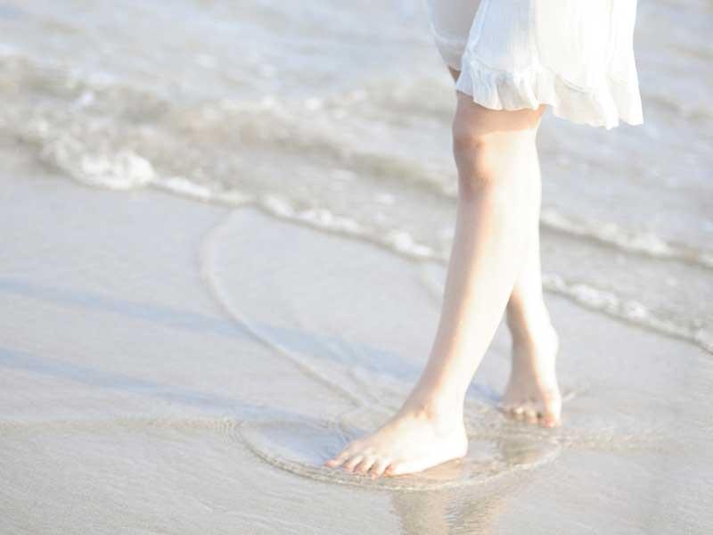 波打ち際で足だけ海に入る妊婦さん