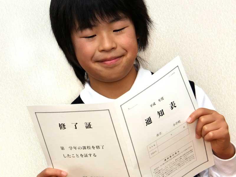 成績の通知表を持っている男の子