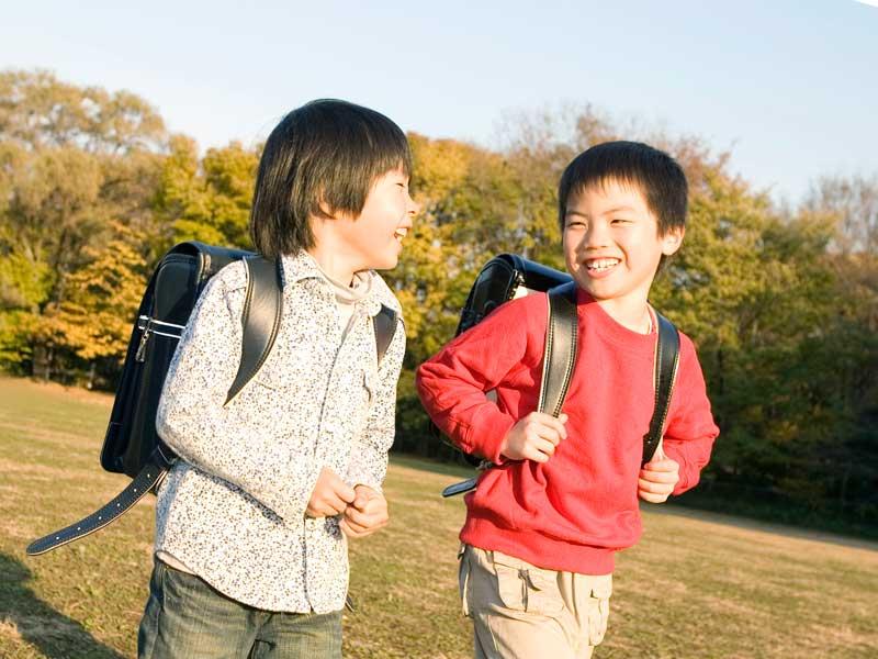 話しながら歩いているランドセルを背負った男の子たち