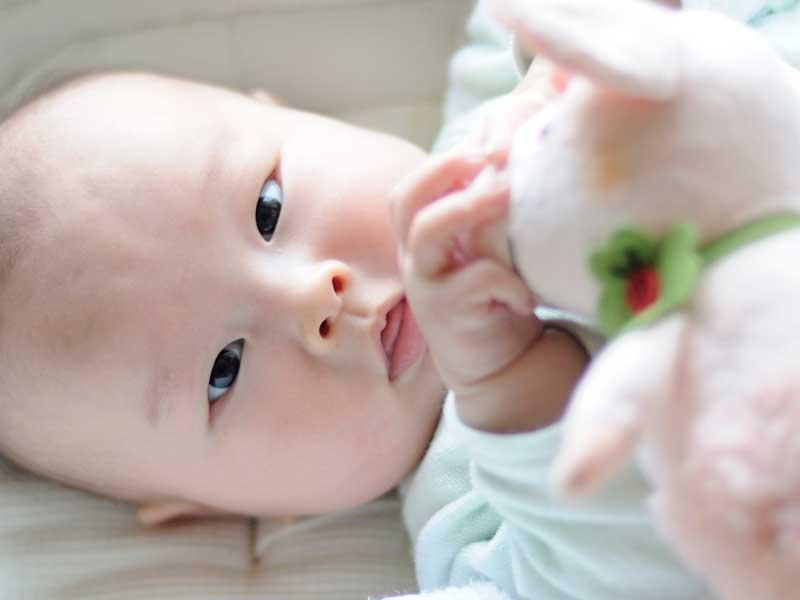 寝転びながらおもちゃで遊んでいる赤ちゃん