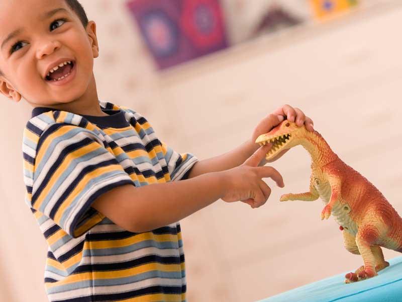 恐竜のおもちゃで遊ぶ子供