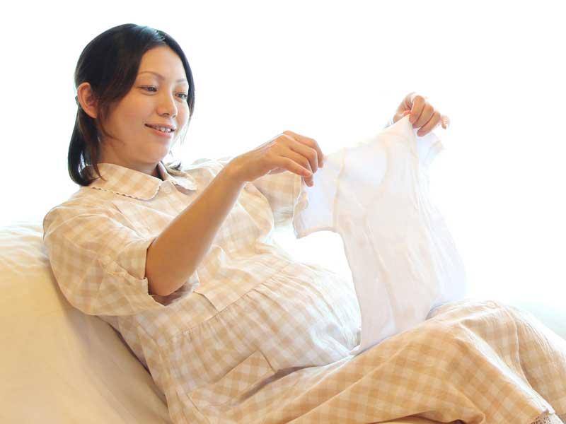 ベビー服を持っている妊婦さん