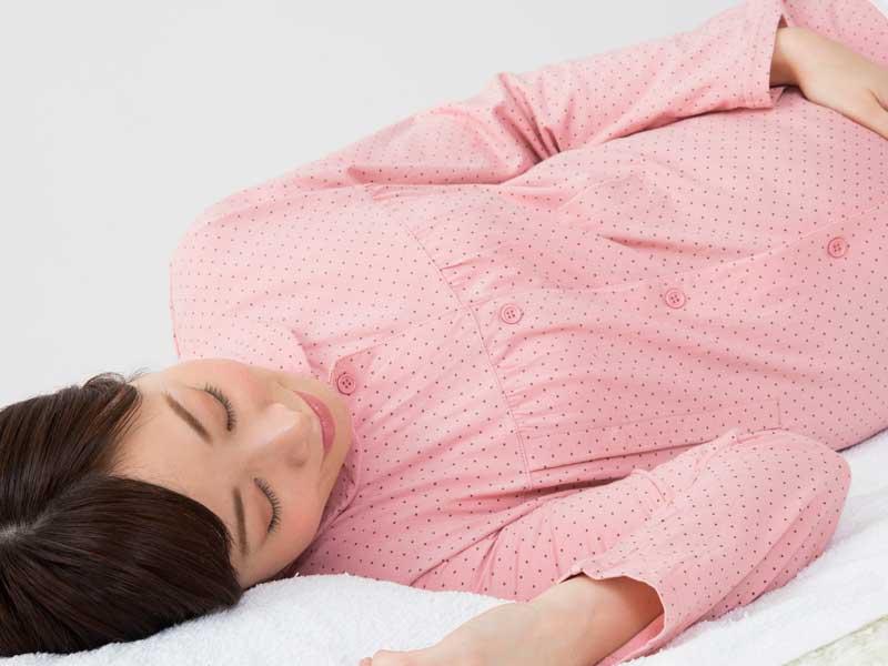 側臥で安静にしている妊婦さん