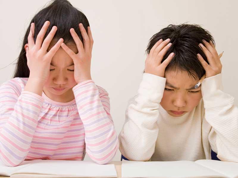 頭を抱えながら勉強している子供達