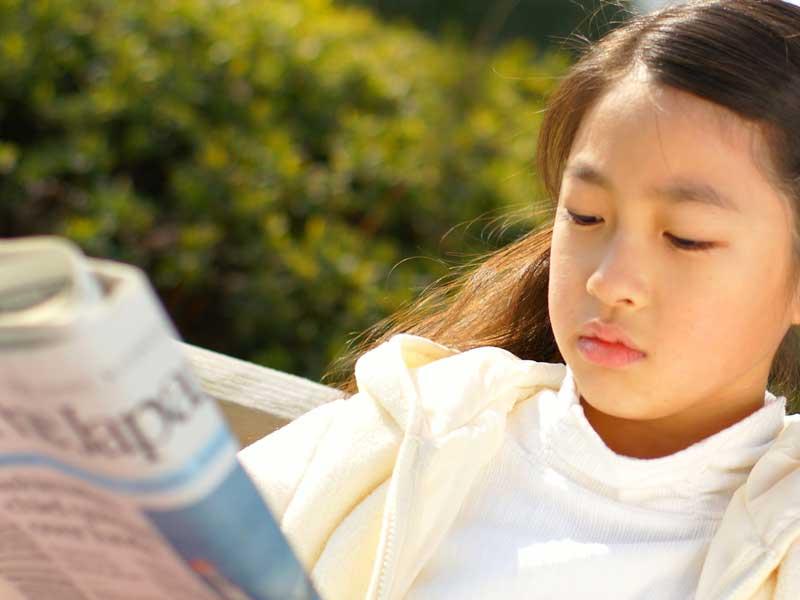 新聞を読んでいる女の子