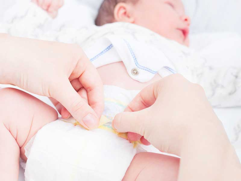 赤ちゃんにおむつ交換するお母さん