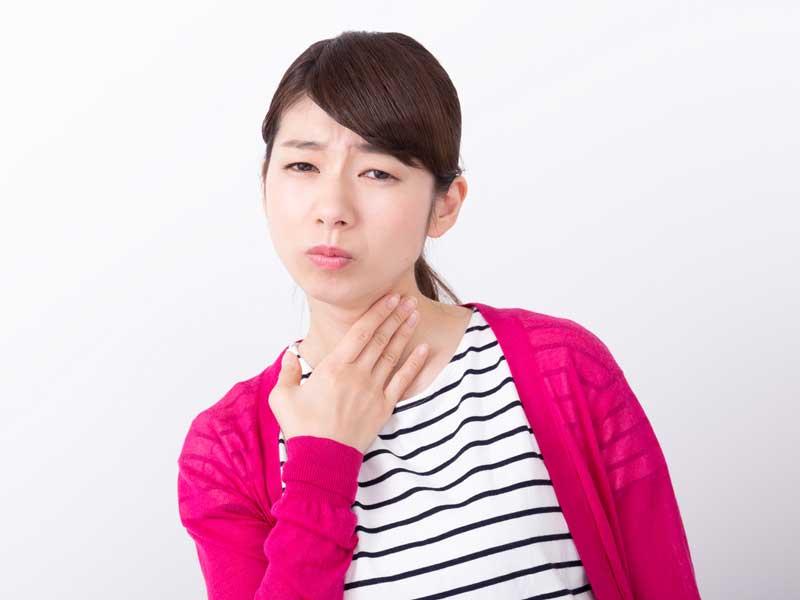喉が痛くておさえている妊婦さん