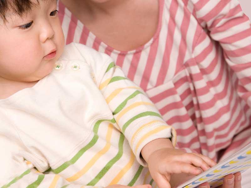 お母さんと絵本を読んでいる子供