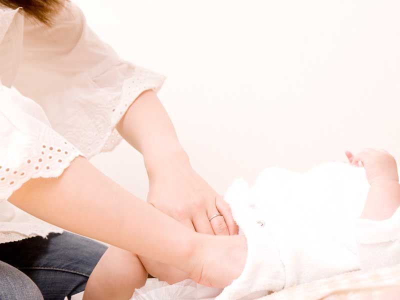 赤ちゃんのおむつを交換するお母さん
