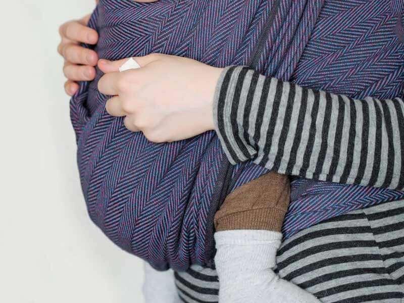 スリングを使って赤ちゃんを抱っこするママ