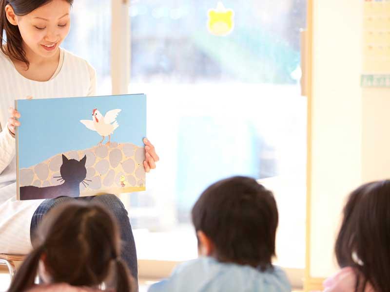 幼稚園の先生が読む絵本を聞いている園児達