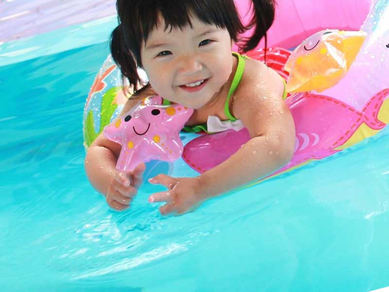幼稚園のプールで遊ぶ子供