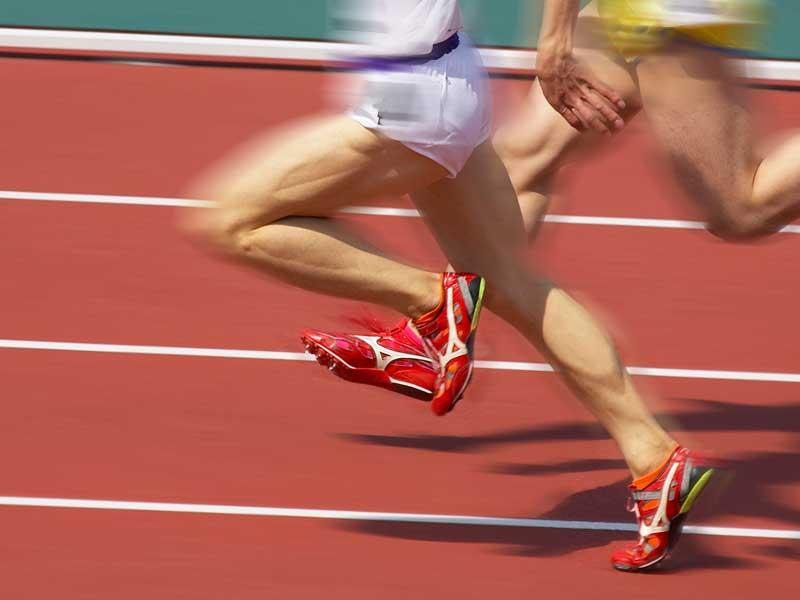 ももを高く上げて走る陸上選手