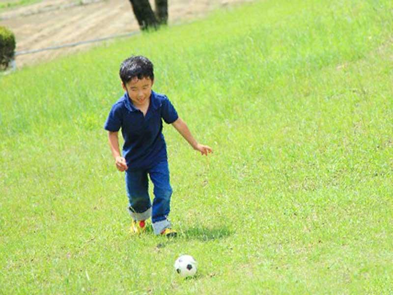 公園でサッカーをしている男の子