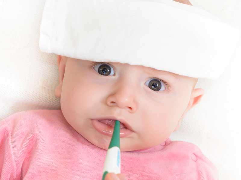熱があって体温計を咥えている赤ちゃん
