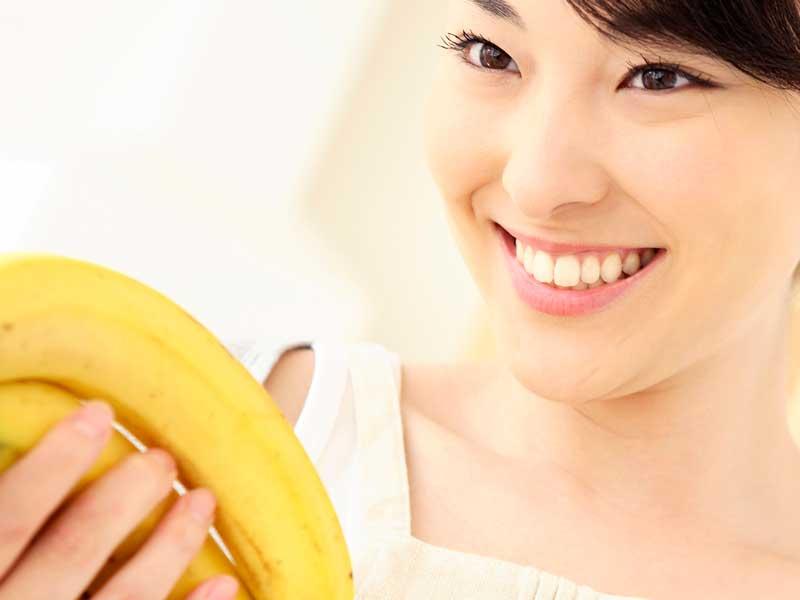バナナを持つ笑顔の妊婦