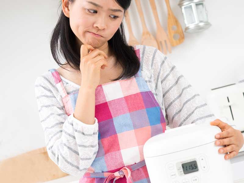 炊飯器を見ながら悩む主婦