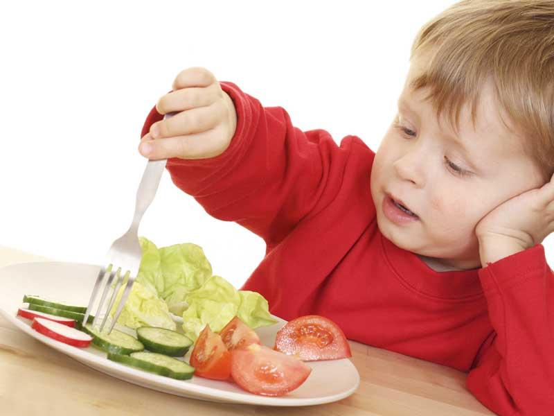 嫌そうな顔をしてフォークで野菜を刺してる子供