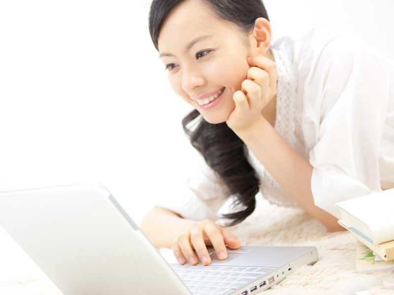 空いた時間でパソコンでネットを見てるママ