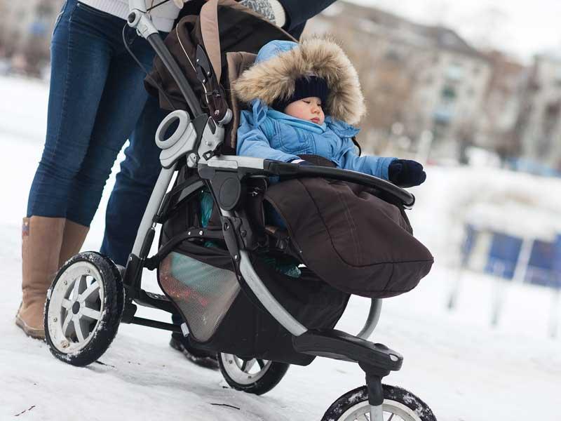 雪が積もってる中でママに連れられてベビーバギーに乗っている赤ちゃん