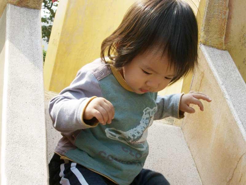 公園の滑り台で遊ぶ男の子