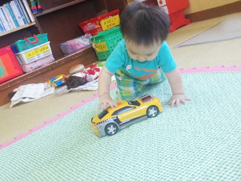 車のおもちゃで遊ぶ幼児