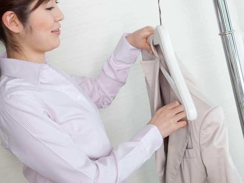 アイロンをかけたスーツをハンガーにかける主婦