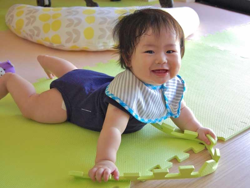 ジョイントマットの上で遊んでいる赤ちゃん
