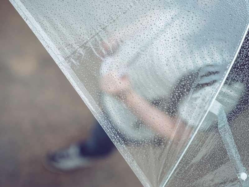 雨の日に傘をさしてる女性