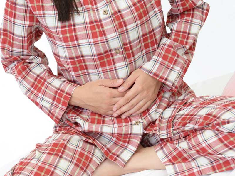 下腹部の痛みに手で抑えている女性