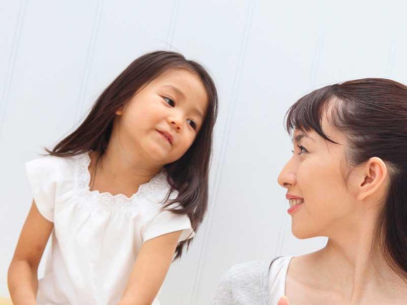 子供の話を聴いているママ