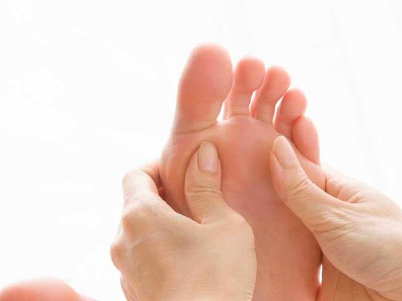 指で押されている足の裏