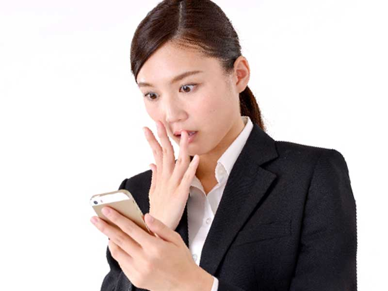 携帯を見てびっくりする女性