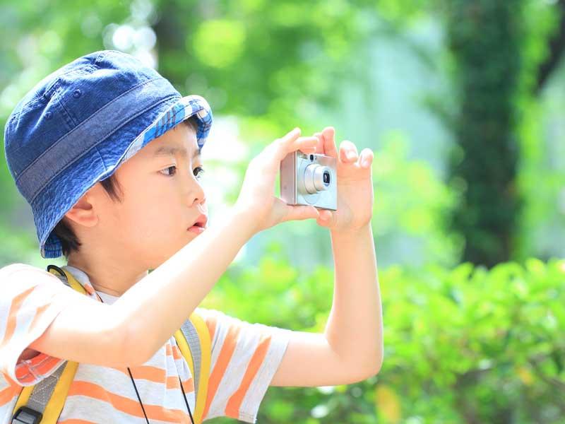 カメラで写真を撮る子供