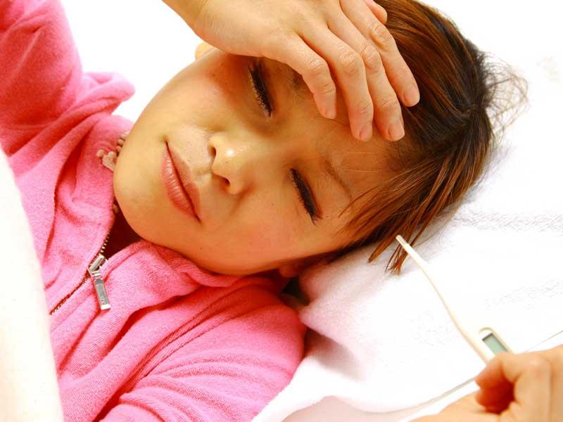 寝ながら熱を測っている妊婦さん