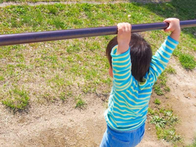鉄棒を握る男の子