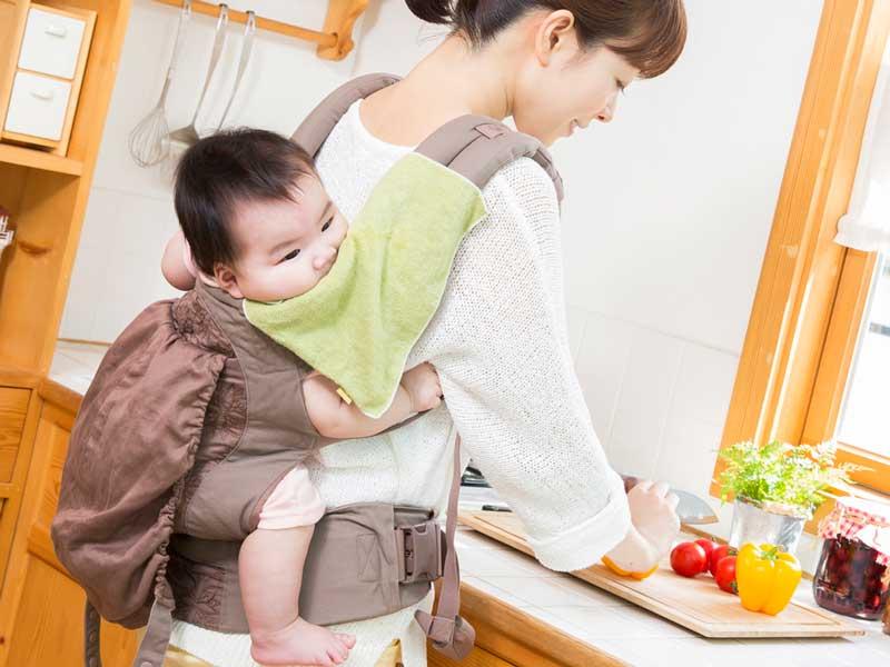 料理しながら赤ちゃんをおんぶしているママ