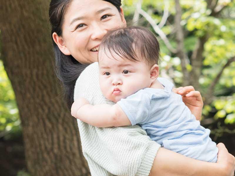 赤ちゃんを連れて散歩するお母さん