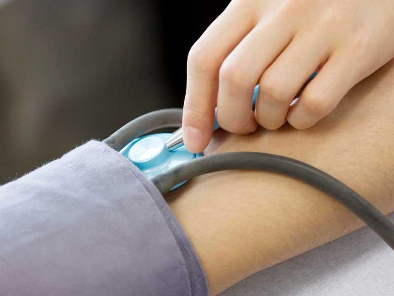 病院で血圧を測ってもらっている妊婦さん